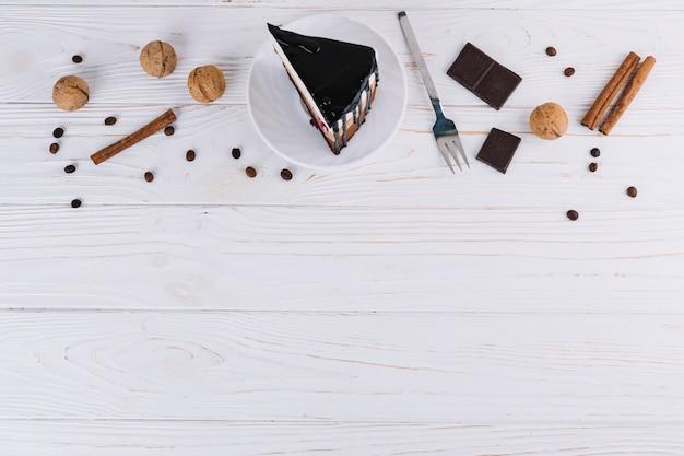 Pasticcino; noci; cannella; chicchi di caffè; forchetta e barretta di cioccolato su sfondo bianco in legno Foto Gratuite