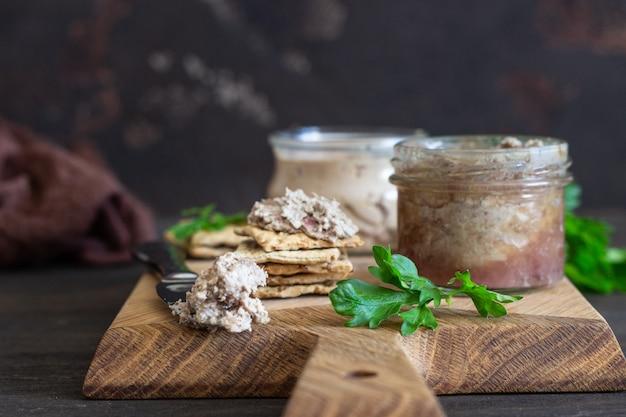 Pasticcio di fegato in un barattolo di vetro con cracker e prezzemolo multigrain. Foto Premium