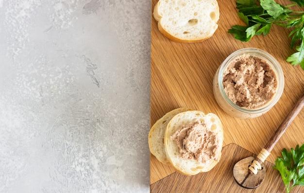 Pasticcio di fegato in un barattolo di vetro con pane fresco e prezzemolo su un tagliere di legno. Foto Premium
