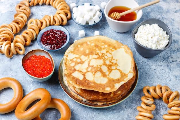 Pasto del festival shrovetide maslenitsa. pancake russo blini con marmellata di lamponi, miele, panna fresca e caviale rosso, zollette di zucchero, ricotta alla luce Foto Gratuite
