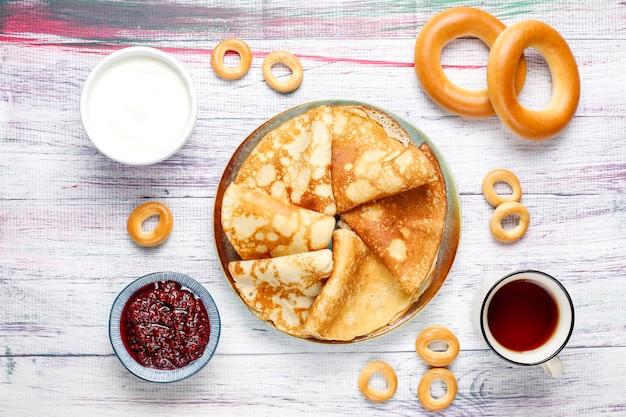 Pasto del festival shrovetide maslenitsa. pancake russo blini con marmellata di lamponi, miele, panna fresca e caviale rosso, zollette di zucchero, ricotta, bubliks su sfondo chiaro Foto Gratuite