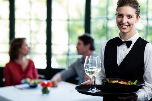 Pasto della cameriera di bar e bicchieri di vino in ristorante Foto Premium