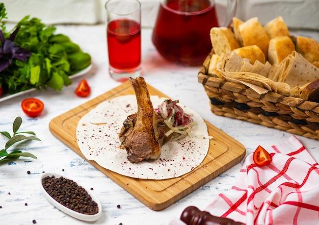 Pasto di agnello di manzo in lavash sul piatto di legno con insalata di cipolle, pane, vegetabels e vino Foto Gratuite