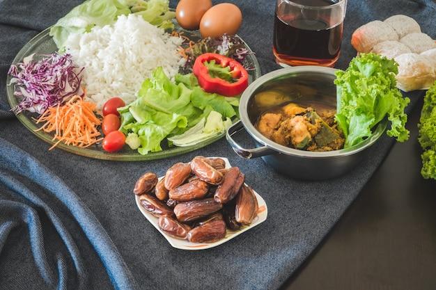 Pasto di iftar e sahoor che serve sul tavolo da pranzo durante il mese sacro del ramadan Foto Premium