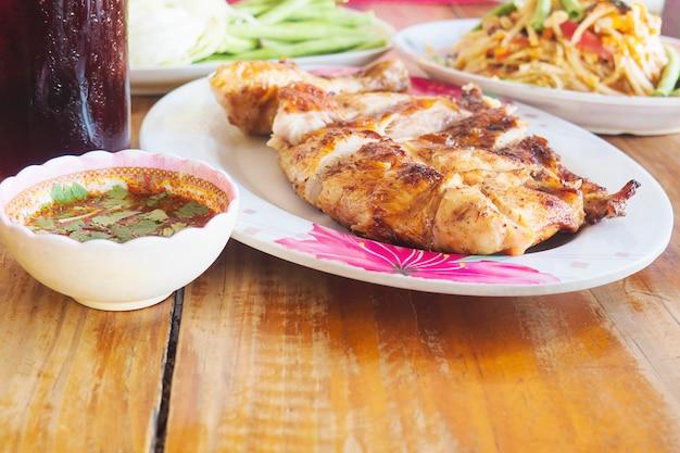 Pasto piccante in stile tailandese, pollo alla griglia con insalata di papaya piccante e bibita fresca Foto Gratuite