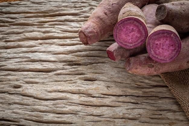Patata dolce porpora disposta su un pavimento di legno marrone. Foto Gratuite