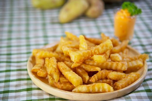 Patata fritta deliziosa sul piatto di legno con salsa tuffata - concetto tradizionale degli alimenti a rapida preparazione Foto Gratuite