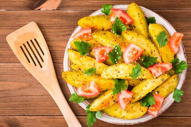 Patate al forno in una buccia con pomodori, erbe, spezie e sesamo in un piatto, vista dall'alto Foto Premium
