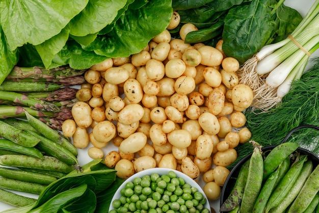 Patate con baccelli verdi, piselli, aneto, cipolle verdi, spinaci, acetosa, lattuga, asparagi distesi su un muro bianco Foto Gratuite
