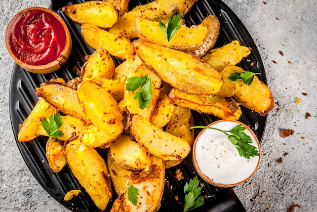 Patate fritte al forno con aglio, erbe aromatiche, salse rosse e bianche Foto Premium