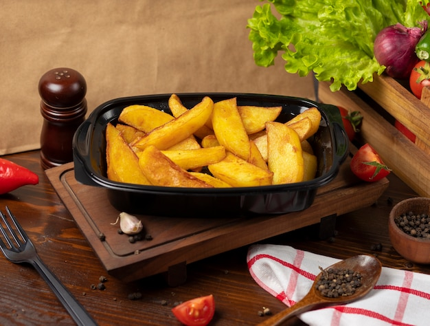 Patate fritte con erbe da asporto in contenitore nero. Foto Gratuite