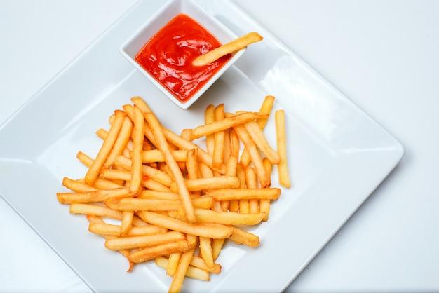 Patate fritte con pomodoro su bianco Foto Premium