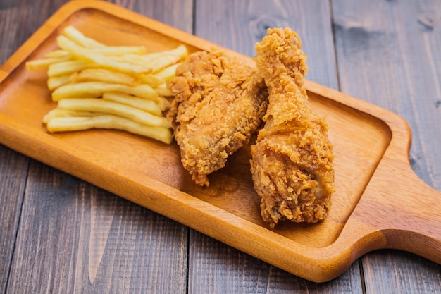Patate fritte croccanti del pollo fritto e delle patate fritte sul piatto di legno Foto Premium