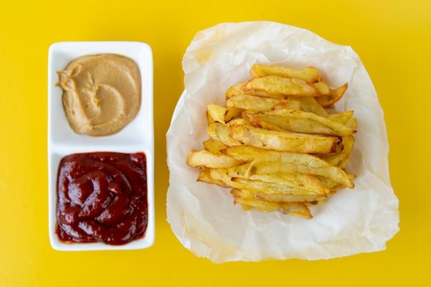 Patate fritte di vista superiore con fondo giallo Foto Gratuite
