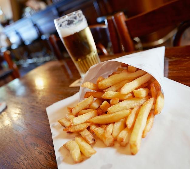 Patate fritte in un sacchetto di carta bianca sul tavolo di legno nel pub di bruxelles Foto Premium