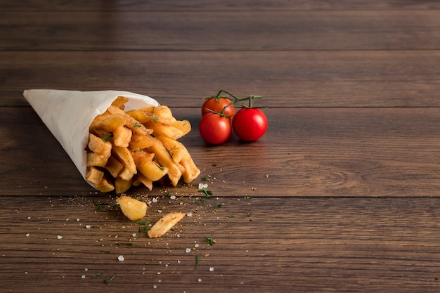 Patate fritte, in un sacchetto di carta su legno marrone Foto Premium