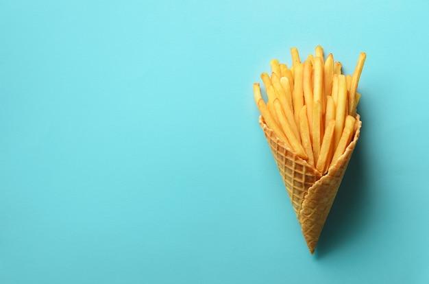 Patate fritte nei coni della cialda su fondo blu. patate fritte salate calde con salsa di pomodoro, foglie di basilico. fast food, cibo spazzatura, concetto di dieta. Foto Premium