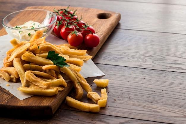 Patate fritte, pomodorini, salsa all'aglio su legno Foto Premium