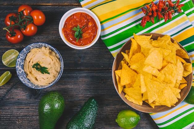 Patatine al nachos messicano; avocado; salsa di salsa; pomodori ciliegini; peperoncini rossi e limone sul tavolo di legno Foto Gratuite