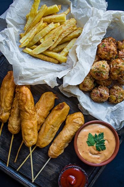 Patatine fritte fritte, corn dog e crocchette di cavolo e patate con salsa e ketchup. Foto Premium