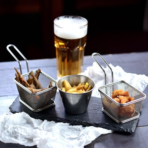 Patatine fritte, pesce fritto e anelli di cipolla in pastella su una tavola di legno, con un bicchiere di birra. spuntini di birra Foto Premium