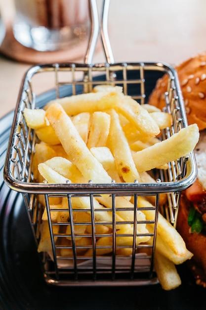 Patatine fritte servite nel cestino di acciaio per mangiare con hamburger. Foto Premium