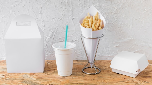 Patatine fritte; tazza di smaltimento e pacchetti sulla scrivania in legno Foto Gratuite