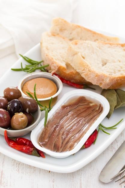 Patè di alici, olive, pane e pesce sul piatto Foto Premium