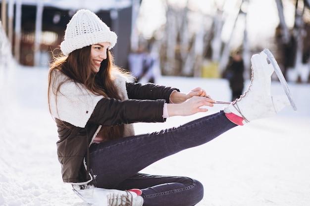 Pattinaggio su ghiaccio della giovane donna su una pista di pattinaggio in un centro urbano Foto Gratuite