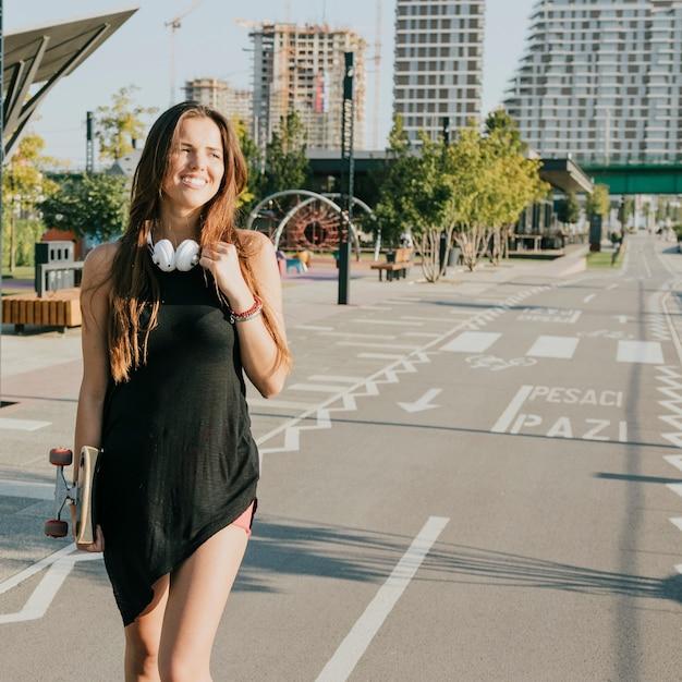 Pattino sorridente della holding della donna che cammina sulla via Foto Gratuite