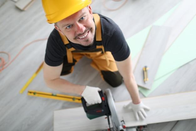 Pavimentazione sorridente del laminato di segatura del casco del carpentiere Foto Premium