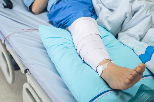 Paziente con bendaggio compressivo bendaggio supporto infortunio sul letto in ospedale di cura. assistenza sanitaria e medica. Foto Premium
