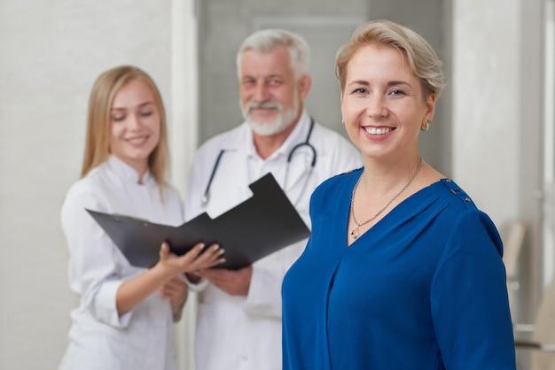 Paziente e medici felici che posano, sorridendo. Foto Premium