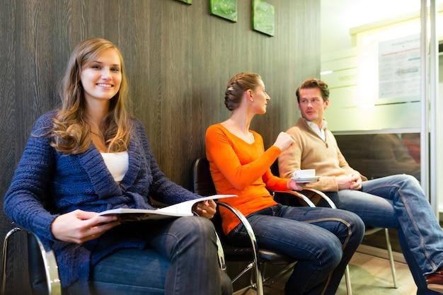 Paziente femminile alla reception della clinica, persone in attesa del suo trattamento Foto Premium