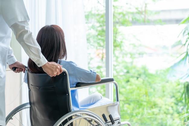 Paziente femminile su sedia a rotelle con medico senior Foto Premium