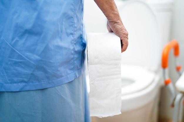 Paziente senior asiatico della donna nella toilette con il tessuto nel reparto di ospedale di professione d'infermiera Foto Premium