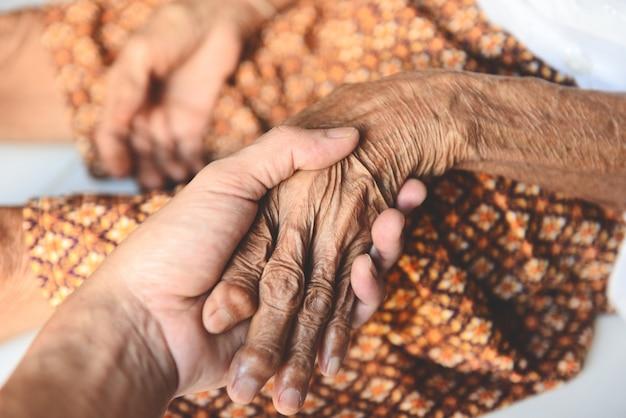 Paziente senior e infermiere misurazione dell'impulso a mano Foto Premium