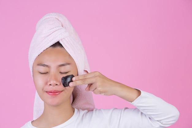Peeling cosmetico di bellezza. giovane femmina con la maschera nera staccata sul prodotto cosmetico della sbucciatura di cura di pelle della pelle sul viso su un rosa. Foto Gratuite