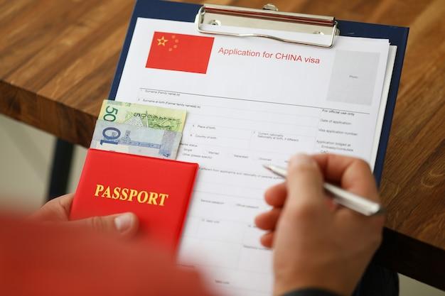 Penna d'argento della stretta maschio della mano con il passaporto Foto Premium