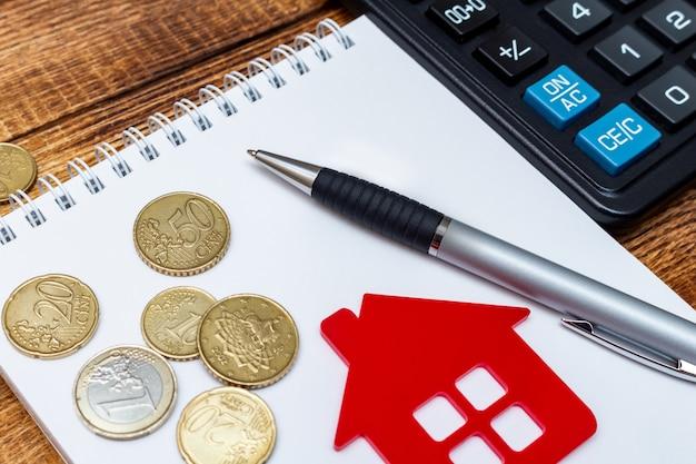 Penna rossa del blocco note della casa domestica sulle banconote e sulle monete Foto Premium