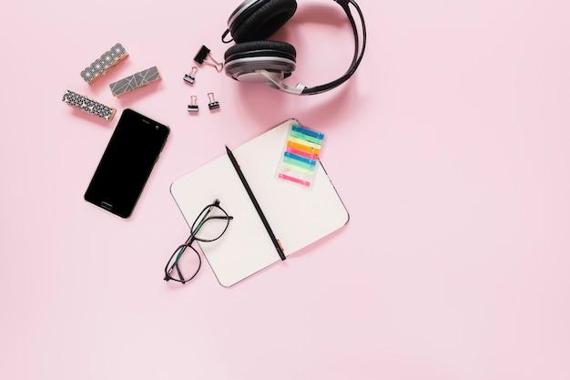 Penna sul diario vuoto; occhiali; e cancelleria con il cellulare su sfondo rosa Foto Gratuite