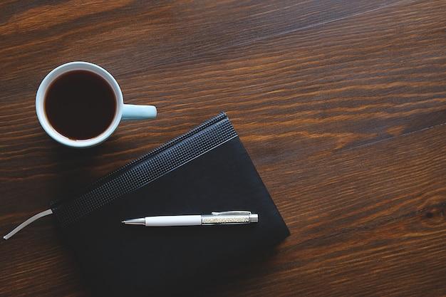 Penna, taccuino o diario, una tazza di tè o caffè su un tavolo di legno. Foto Premium