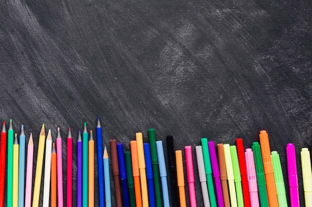 Pennarelli e matite luminose in fondo a uno sfondo scuro Foto Gratuite
