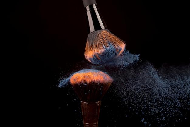 Pennelli trucco e polvere brillante su sfondo scuro Foto Gratuite