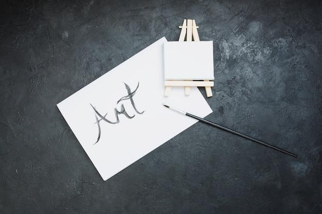 Pennello; mini cavalletto e carta di testo arte su sfondo nero Foto Gratuite