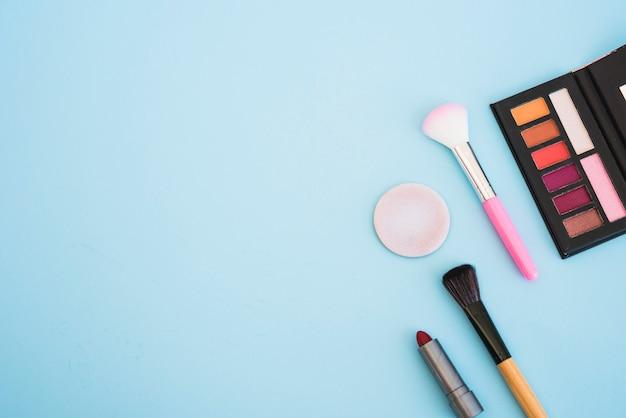 Pennello per ombretti per il trucco; spugna; rossetto su sfondo blu Foto Gratuite
