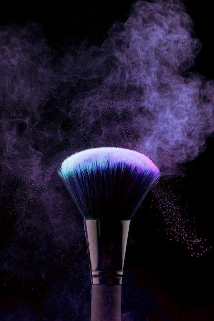 Pennello trucco con spruzzi di polvere viola Foto Gratuite