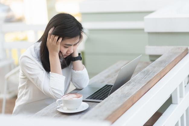 Pensiero duro delle donne lavoratrici e lavorare con il computer portatile nel caffè Foto Premium