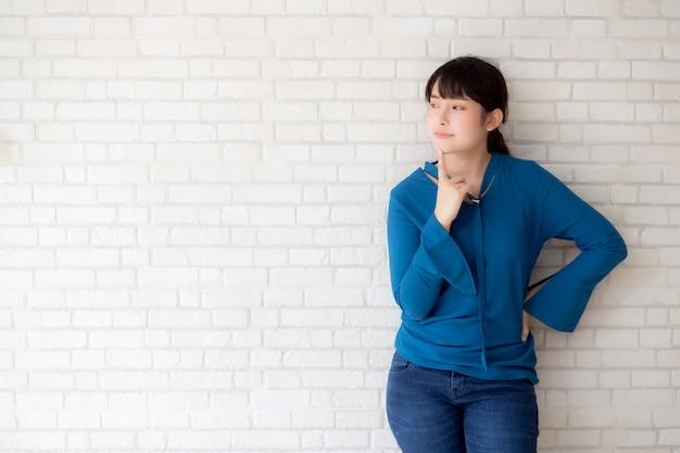 Pensiero sicuro della giovane donna asiatica del bello ritratto con il fondo del calcestruzzo e del cemento Foto Premium