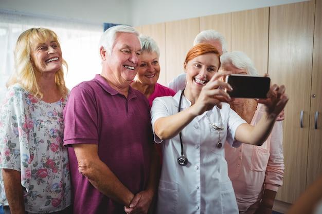 Pensionati che prendono un selfie con un'infermiera Foto Premium